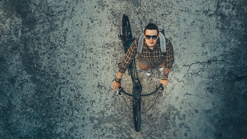 Young Male Cyclist Riding On Bike Down The Street, Top View. Daily Lifestyle Urban Resting Concept. Young Man Cyclist In Glasses With Backpack Riding On Bike royalty free stock photos