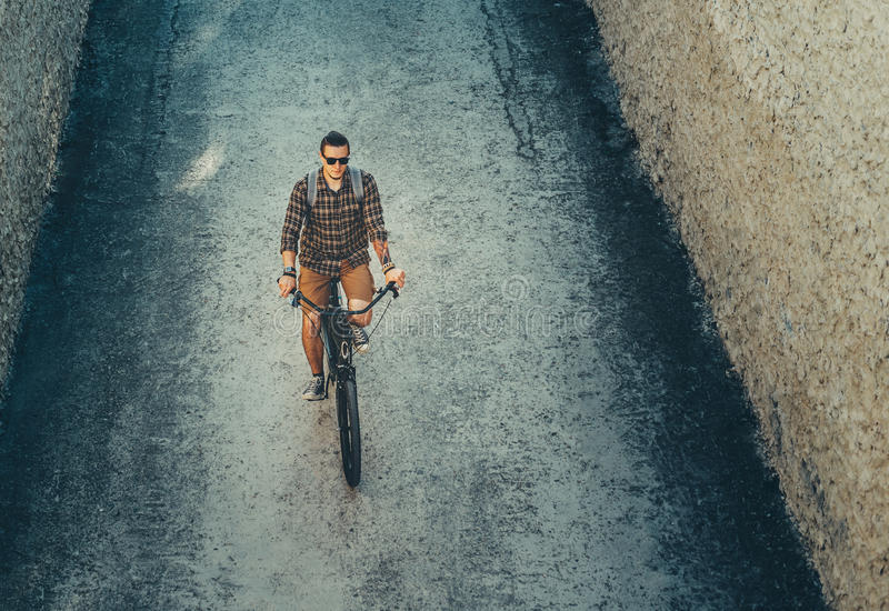 Young Male Cyclist Riding On Bike Down The Street, Top View. Daily Lifestyle Urban Resting Concept. Young Man Cyclist In Glasses With Backpack Riding On Bike royalty free stock image