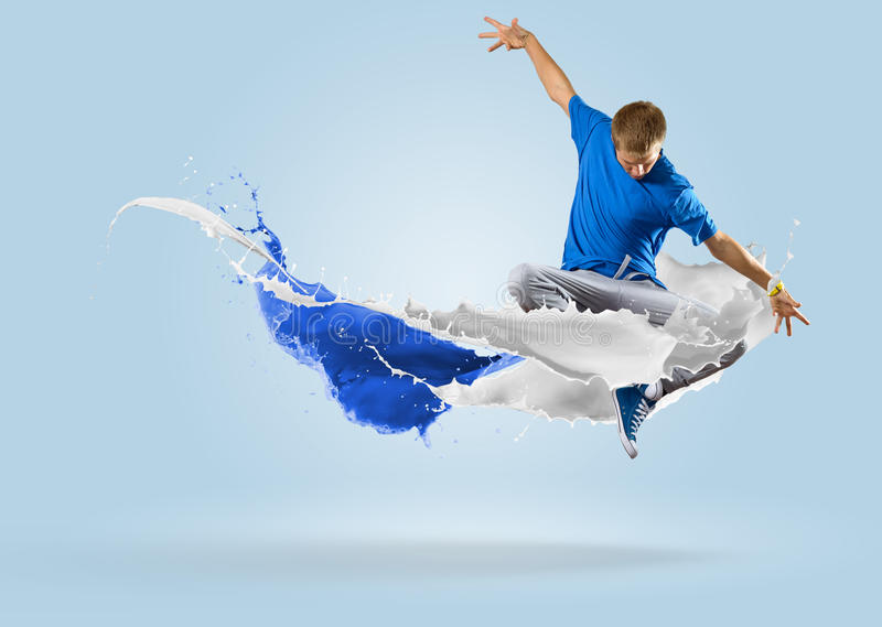 Young male dancer jumping with splash of paint. Young male dancer jumping surrounded by splashes of paint stock images