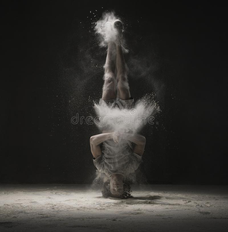 Young dancer doing a headstand in dust cloud view stock images