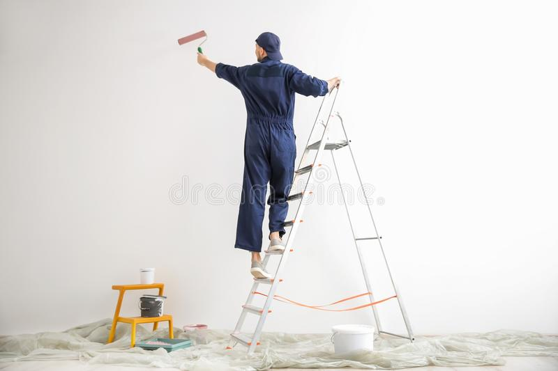 Young male decorator painting wall royalty free stock image