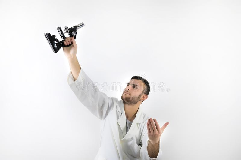Young male doctor with beard holding up a microscope isolated on white background. Holding up a microscope isolated on white background royalty free stock image