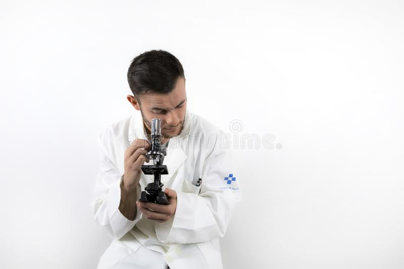 Young male doctor with beard looking through microscope isolated on white background. Looking through microscope isolated on white background royalty free stock photos