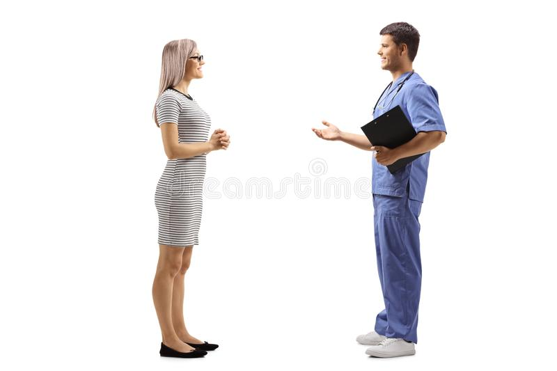 Young male doctor in a blue uniform talking to a young woman royalty free stock photos