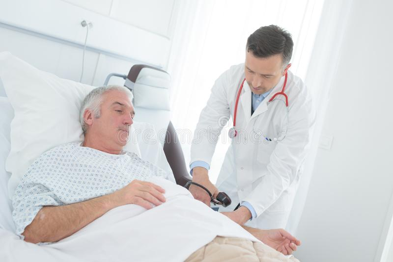 Young male doctor checking blood pressure senior male patient stock photo