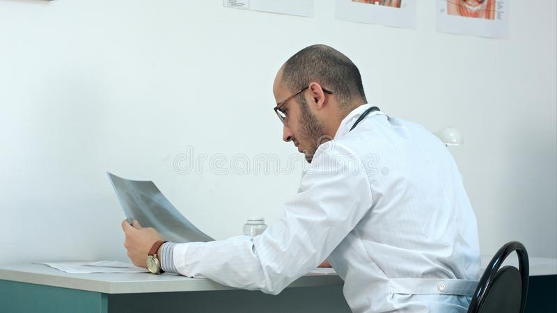 Young male doctor examining chest xray image stock images