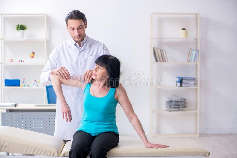 Young male doctor examining old female patient. The young male doctor examining old female patient royalty free stock image