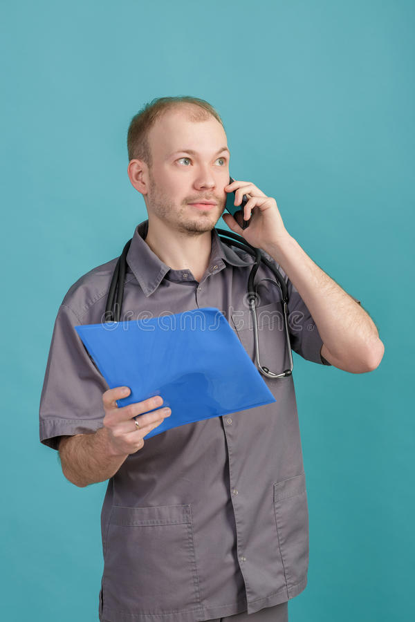 Young male doctor holding a folder with papers and talking on the phone on blue background. Young male doctor holding a folder with papers and talking on the stock images