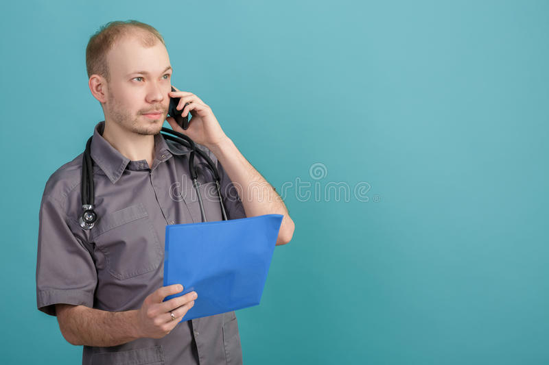 Young male doctor holding a folder with papers and talking on the phone on blue background. Young male doctor holding a folder with papers and talking on the stock image