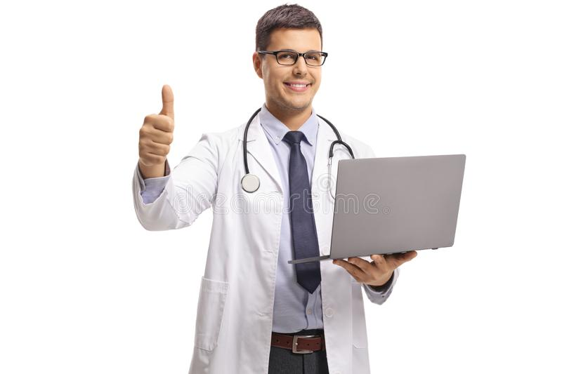Young male doctor holding a laptop computer and showing thumbs up stock photo