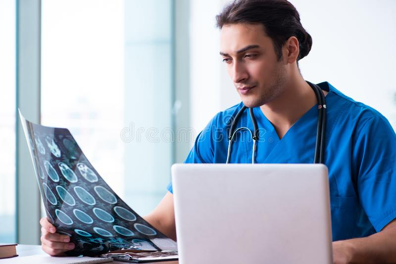 Young male doctor looking at x-ray images. The young male doctor looking at x-ray images royalty free stock images