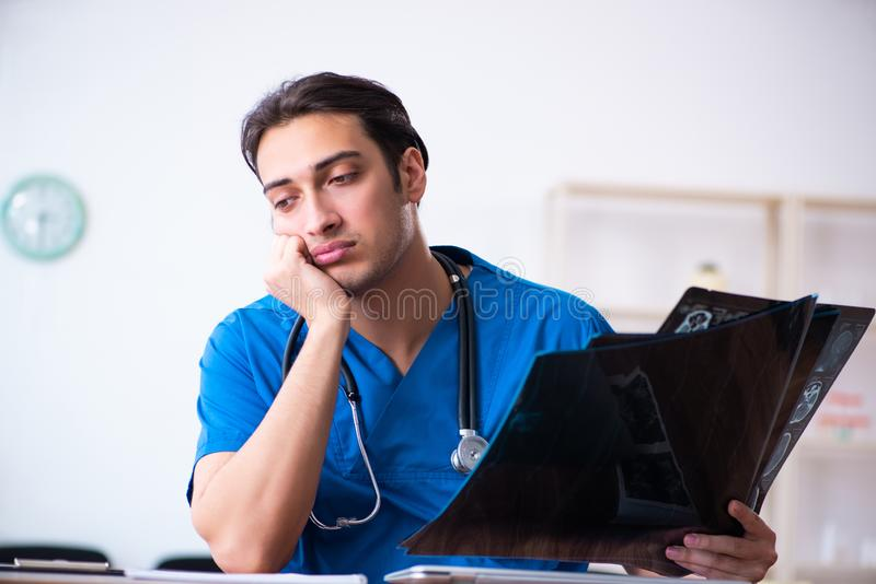 Young male doctor looking at x-ray images. The young male doctor looking at x-ray images stock image