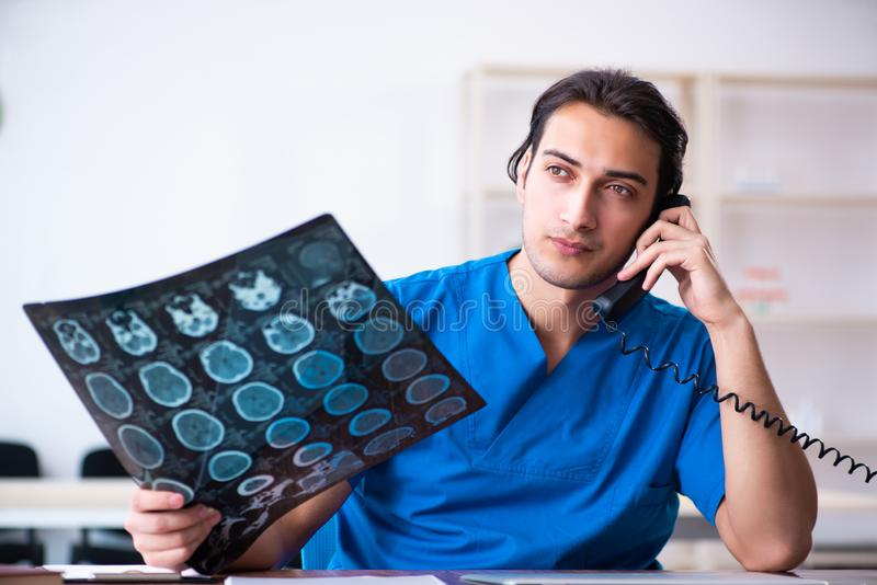 Young male doctor looking at x-ray images. The young male doctor looking at x-ray images stock photography