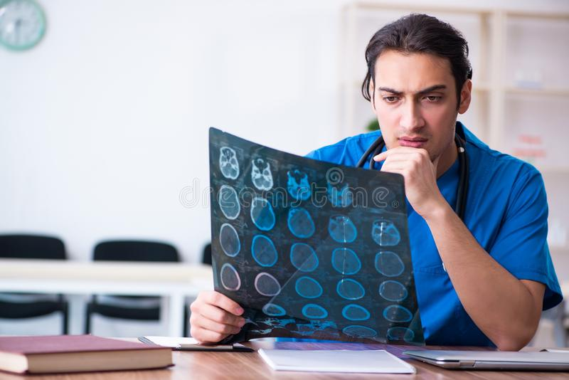 Young male doctor looking at x-ray images royalty free stock photography