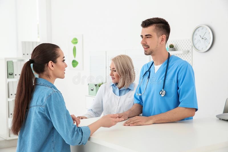 Young male doctor and senior female receptionist stock photography