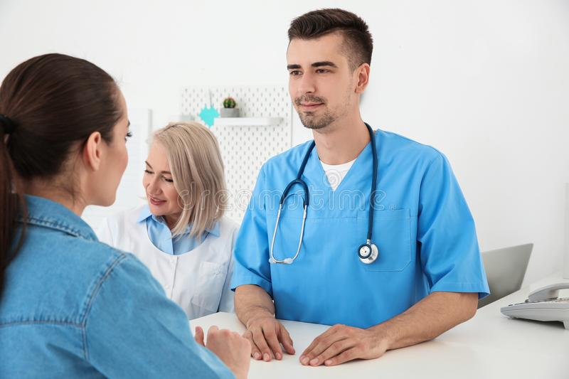 Young male doctor and senior female receptionist. Working with client in hospital royalty free stock photo