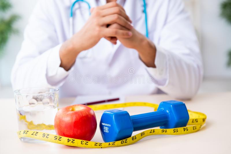 Young male doctor in sport and dieting concept. The young male doctor in sport and dieting concept royalty free stock photography