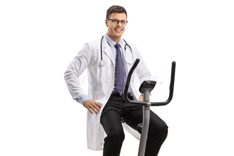 Young male doctor on a stationary bike looking at the camera and smiling royalty free stock photos