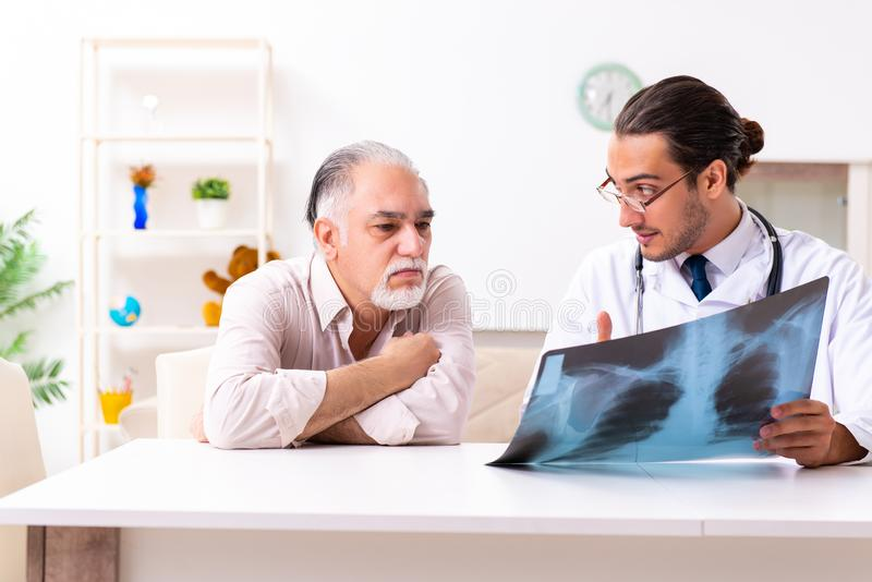 Young male doctor visiting old patient at home. The young male doctor visiting old patient at home stock image