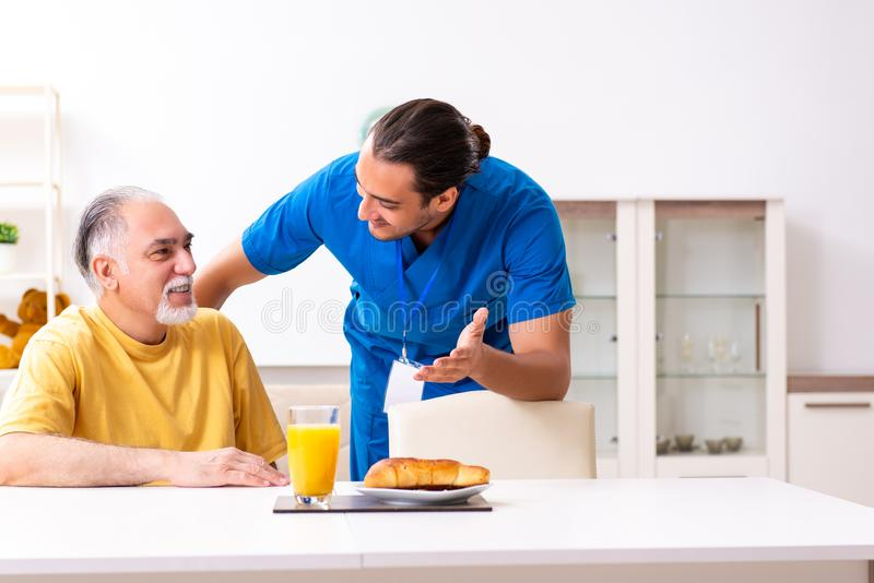Young male doctor visiting old patient at home. The young male doctor visiting old patient at home royalty free stock photos