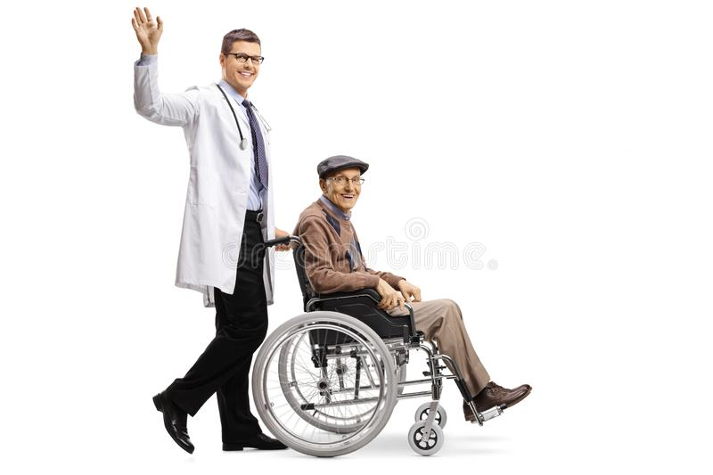 Young male doctor waving and pushing an elderly male patient in a wheelchair stock photography
