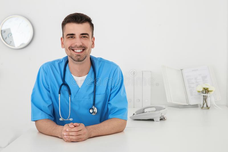 Young male doctor working at reception desk. In hospital stock photo