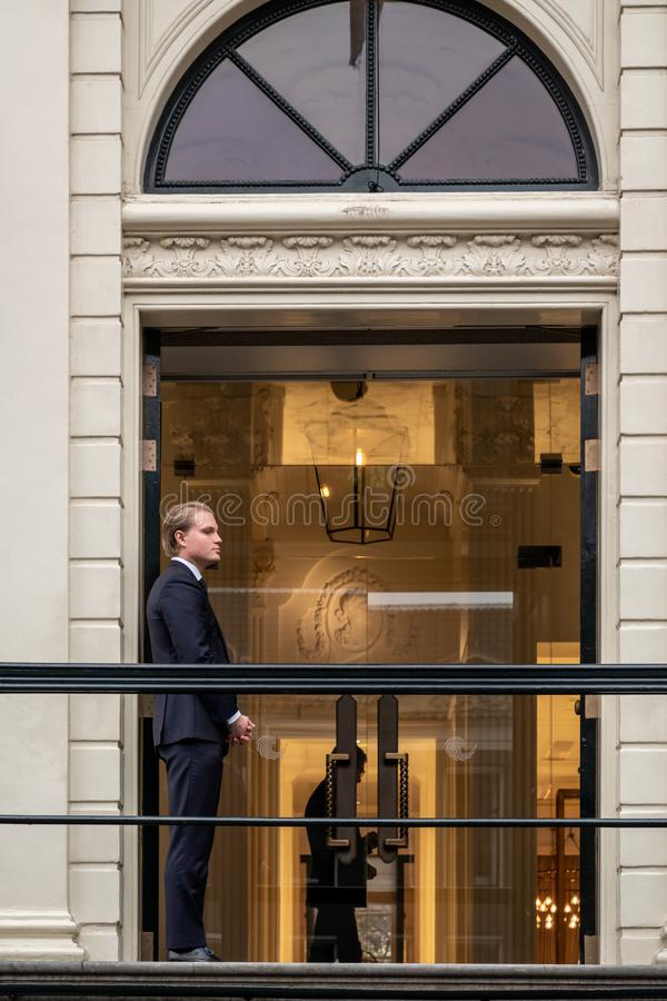 Young male doorman at a hotel entrance in Amsterdam. stock photo