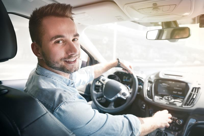 Young male driver behind the wheel. Sharing economy service or taxi driver concept stock photo