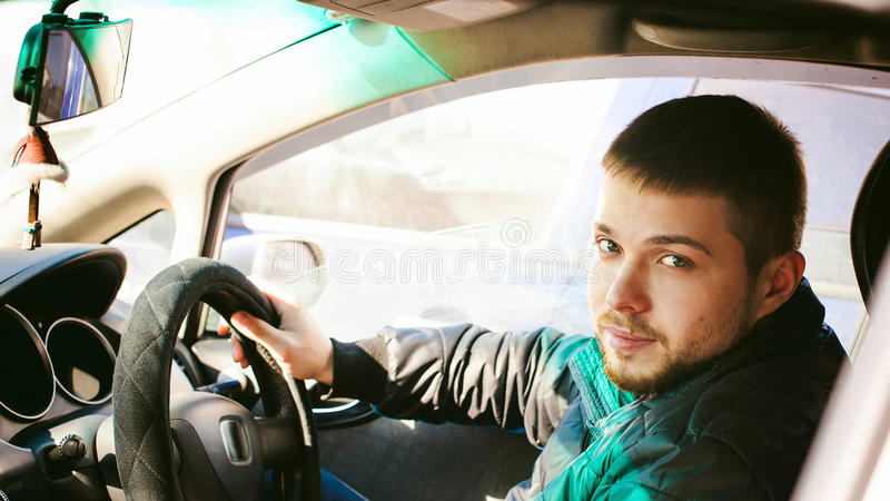 Young male driver sits holding his hand behind the wheel in the salon of his car. A happy look of a bearded motorist man royalty free stock images