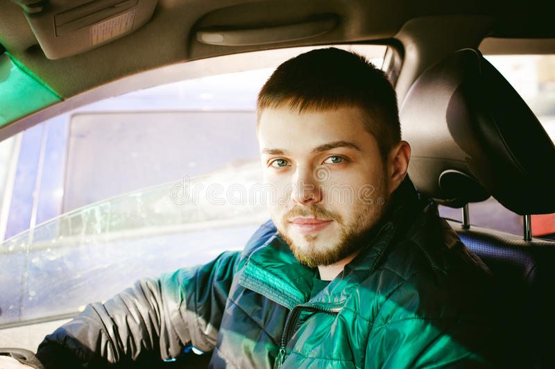 Young male driver sits holding his hand behind the wheel in the salon of his car. A happy look of a bearded motorist man stock photos