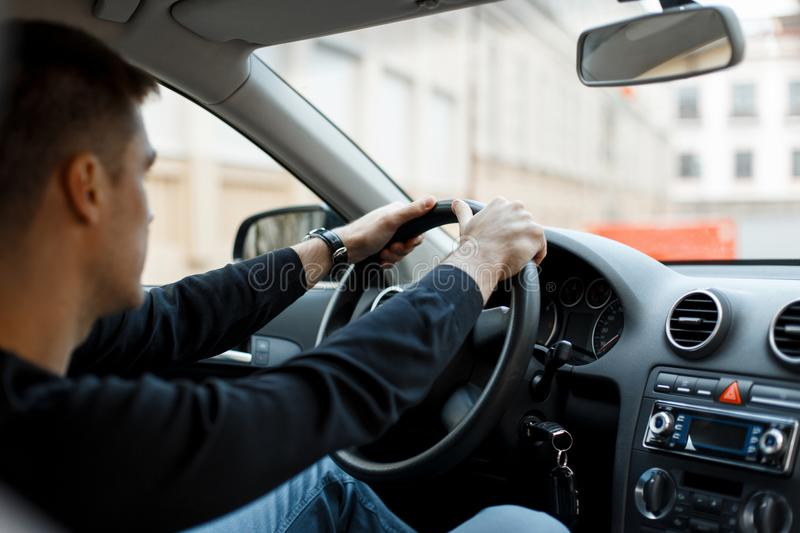 Young male driver sitting in the car and holding the wheel. royalty free stock photo