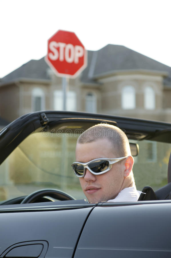Young male driver at stop sign. Young male driver in convertible at a stop sign stock photo