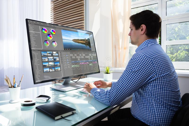 Editor editing video on computer. Young male editor editing video on computer at workplace royalty free stock images