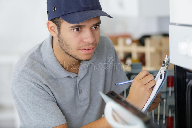Young male electrician writing on clipboard while looking at oven royalty free stock image