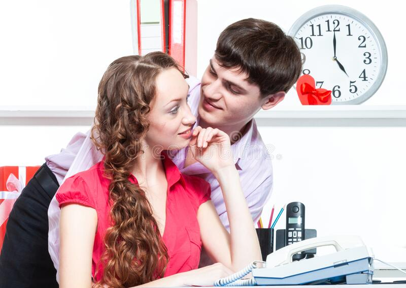 A young male employee of the company gave flowers and shows courtship to his colleague-a young woman with curly hair. Lovers flirt. A young male employee of the royalty free stock image