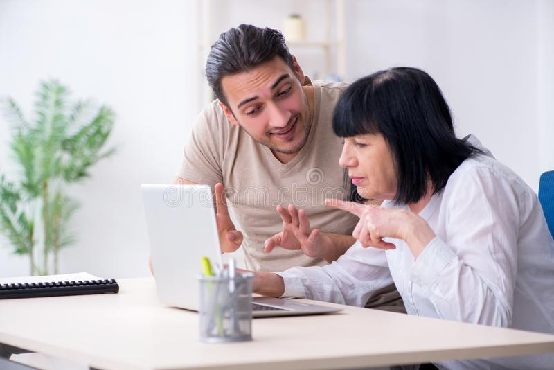 Young male employee explaining to old female colleague how to us. E computer royalty free stock images