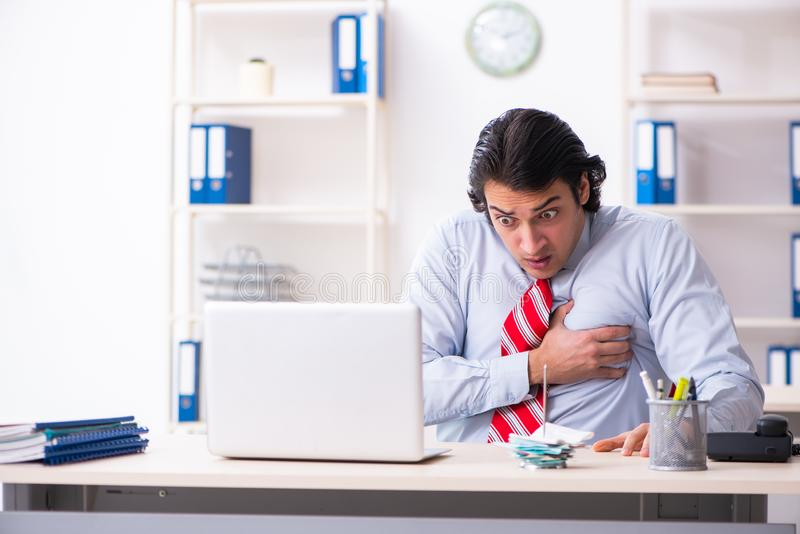 Young male employee suffering in the office. The young male employee suffering in the office stock images