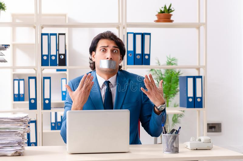Young male employee with tape on the mouth. The young male employee with tape on the mouth royalty free stock photography