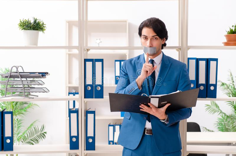 Young male employee with tape on the mouth. The young male employee with tape on the mouth royalty free stock image