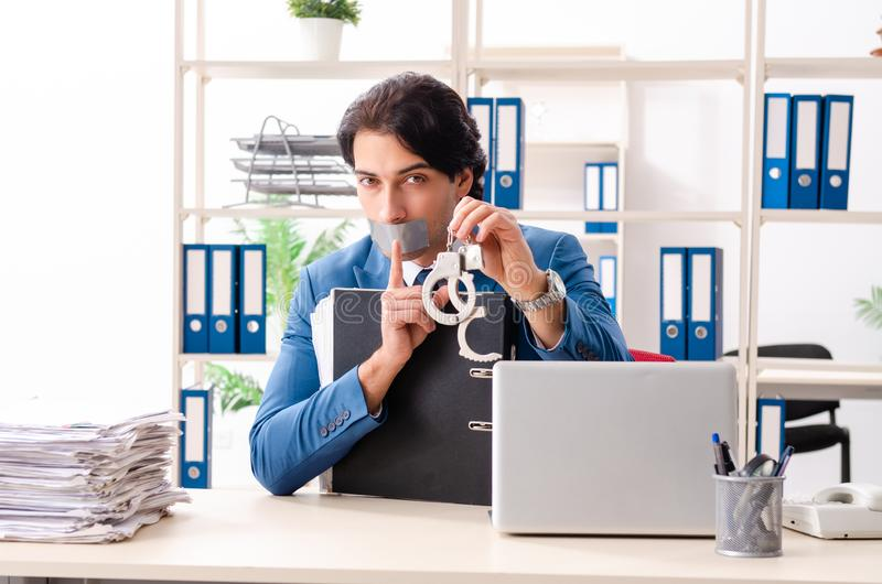 Young male employee with tape on the mouth. The young male employee with tape on the mouth stock image