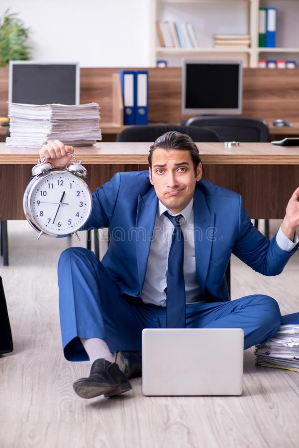 Young male employee and too many work in the office. The young male employee and too many work in the office royalty free stock photography