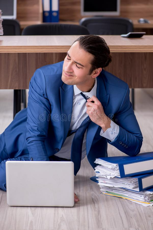 Young male employee and too many work in the office. The young male employee and too many work in the office stock photo