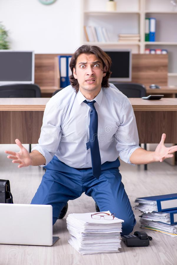 Young male employee and too many work in the office. The young male employee and too many work in the office stock image