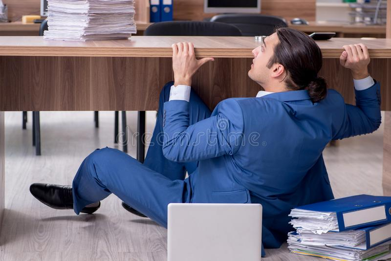 Young male employee and too many work in the office. The young male employee and too many work in the office royalty free stock images