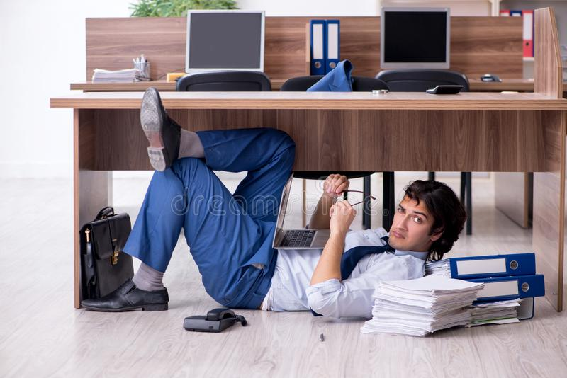 Young male employee and too many work in the office. The young male employee and too many work in the office royalty free stock photos