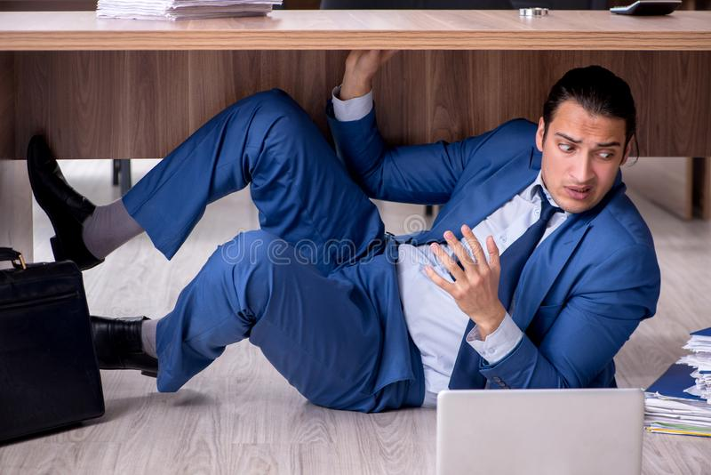 Young male employee and too many work in the office. The young male employee and too many work in the office stock photography