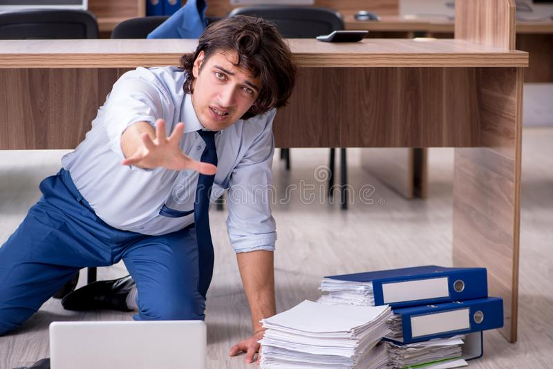 Young male employee and too many work in the office royalty free stock photos