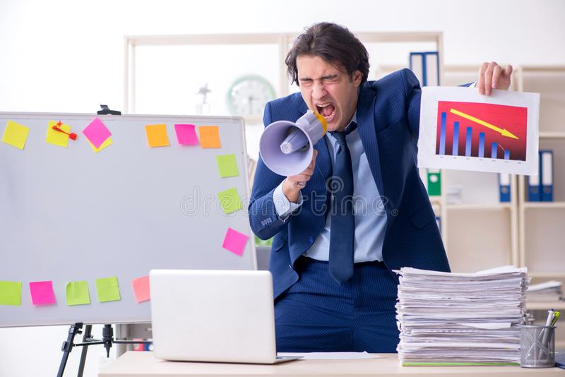 Young male employee unhappy with excessive work stock image