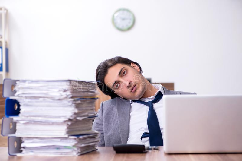 Young male employee unhappy with excessive work. The young male employee unhappy with excessive work royalty free stock photo