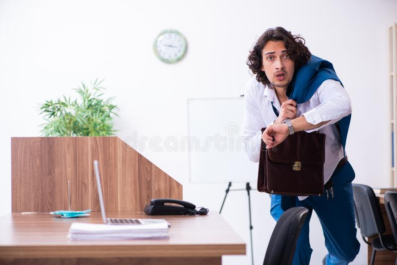 Young male employee unhappy with excessive work. The young male employee unhappy with excessive work stock photo